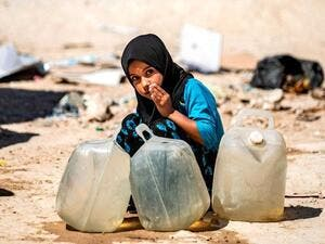 A displaced Syrian girl washes her mouth at Al Hol camp for the internally displaced people in Al Hasakeh governorate in northeastern Syria (AFP photo)