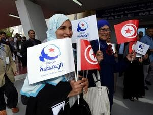 A file photo shows supporters of Tunisia's Islamist Ennahdha Party wave the national flag and the party flag during the opening of Ennahdha in Tunis. (AFP)