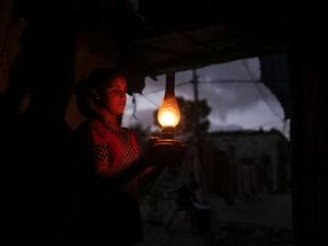 A Palestinian girl uses a gas lamp during a power cut after Gaza's sole power plant shut down amid tension with Israel, in an impoverished household in Khan Yunis in the southern Gaza Strip, on August 18, 2020. MAHMUD HAMS / AFP