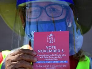 A Democratic Party canvasser holds up campaign material while knocking on doors in the suburbs of Phoenix, Arizona, October 15, 2020 to encourage people to vote in the November 3 presidential and congressional elections. The canvassers, many of whom lost their jobs in LA because of the pandemic, earn up to 20 dollars an hour and keep their health insurance. Their main focus has been to zoom in on working-class neighborhoods where voter turnout is usually low, but the Biden activists also venture into more w