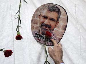 In this file photo taken on November 28, 2016 a man touches a portrait of late Kurdish lawyer Tahir Elci, displayed next to red flowers (carnations) in Diyarbakir, during a ceremony in tribute to the lawyer, near the historical mosque where he was shot dead last year. A long-awaited trial opened on October 21, 2020, of three police officers for the 2015 killing of a prominent rights lawyer in Diyarbakir, Turkey's biggest Kurdish-majority city. Tahir Elci, who campaigned for Kurdish rights, was shot in the