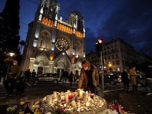 People lights candle outside the Notre-Dame de l'Assomption Basilica in Nice on October 30, 2020, a day after a knife attacker killed three people, cutting the throat of two, inside the church of the French Riviera city, and police arrest a young Tunisian migrant from Sfax who arrived in Europe only last month, according to French prosecutors. (AFP/File)
