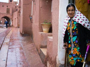 lady in traditional clothes in the ancient village of Abyaneh, near Kashan, in Iran. In background, the typical red mud-brick houses of Abyaneh  (Shutterstock)