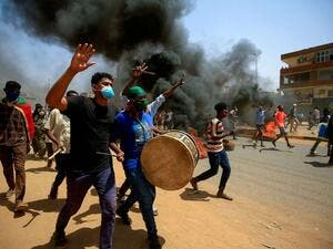 Sudanese demonstrators carrying a drum gesture as smoke billows from burning tires during a protest east of the capital Khartoum, Sudan, June 30, 2020. Ashraf Shazly/AFP via Getty Images, FILE