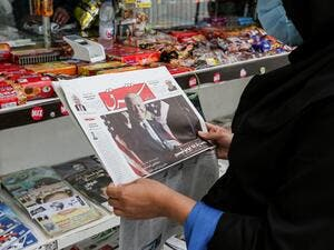 A woman browses the front page of Iranian Farsi newspaper Shargh featuring the 2020 US general election results at a news stand in Iran's capital Tehran on November 8, 2020. ATTA KENARE / AFP