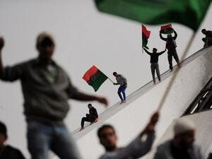 "In this file photo taken on March 2, 2011, Libyans wave their old national flag as others celebrate burning copies of the ""green book"" authored by Libyan ruler Moamer Kadhafi, in the north-central Libyan city of Benghazi. Ten years ago, a wildfire of revolts in the Arab world touched off an unlikely series of events that swelled, then dashed many hopes, and irrevocably changed the region. ROBERTO SCHMIDT / AFP"