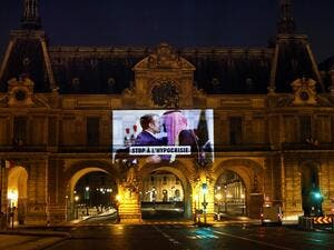 "This picture taken early on November 19, 2020, shows a projection on the Louvre Museum in Paris by Amnesty International members depicting French President Emmanuel Macron greeting Saudi Crown Prince Mohammed bin Salman and reading ""Stop hypocrisy"", ahead of the upcoming virtual G20 summit. THOMAS COEX / AFP"