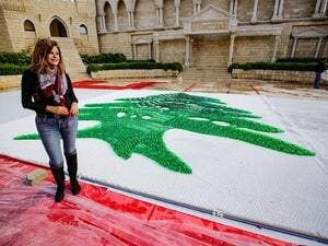 Caroline Chaptini, an environmental activist, poses next to a partially-completed 300-square-metre Lebanese national flag made up from plastic bottles, caps, and empty bullet cartridge set up by activists at an open-air restaurant and wedding venue in the town of Bnachii in northern Lebanon on November 21, 2020, a day ahead of the country's 77th independence day. Ibrahim Chalhoub / AFP