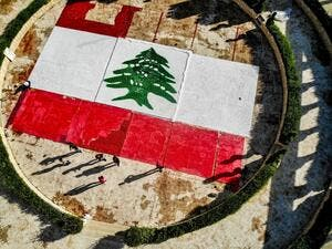 This picture taken on November 21, 2020 shows an aerial view of a partially-completed 300-square-metre Lebanese national flag made up from plastic bottles, caps, and empty bullet cartridge set up by environmental activists at an open-air restaurant and wedding venue in the town of Bnachii in northern Lebanon, a day ahead of the country's 77th independence day. Ibrahim Chalhoub / AFP