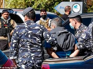 The police in Beirut confirmed 15 inmates has been re-arrested so far and four had handed themselves in. Pictured: Police escort a prisoner who had fled a detention centre. (AFP)