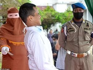 A child rapist cries out and grimaces as he is publicly flogged by a member of the sharia police after he was found guilty of raping and molesting a minor in Indonesia's ultra-conservative Aceh province. AFP