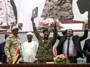 "In this file photo taken on August 17, 2019, Sudan's protest leader Ahmad Rabie (2nd-R), flashes the victory gesture alongside General Abdel Fattah al-Burhan (C), the chief of Sudan's ruling Transitional Military Council (TMC), during a ceremony where they signed a ""constitutional declaration"" that paves the way for a transition to civilian rule, in the capital Khartoum, accompanied by General Mohamed Hamdan Daglo ""Hemeti"" (2nd-L), TMC deputy chief and commander of the Rapid Support Forces (RSF) paramilitar"