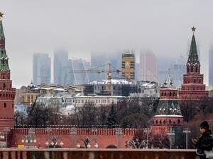 A woman walks in front of the Kremlin and skyscrapers of the Moscow International Business Centre (Moskva City) in Moscow on December 17, 2020. Yuri KADOBNOV / AFP