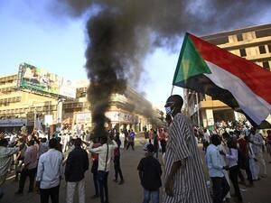 A Sudanese man wearing a face mask waves his country's national flag during protests in the capital Khartoum to mark the second anniversary of the start of a revolt that toppled the previous government, on December 19, 2020. Frustrated by the lack of change in their daily lives, thousands of demonstrators, mostly young, marched in several towns in Sudan. ASHRAF SHAZLY / AFP