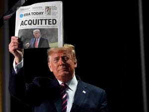 "US President Donald Trump holds up a newspaper that displays a headline ""Acquitted"" as he arrives to speak at the 68th annual National Prayer Breakfast on February 6, 2020 in Washington,DC. President Donald Trump said Thursday that he suffered a ""terrible ordeal"" during his impeachment.  Nicholas Kamm / AFP"