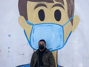 A Palestinian man sits in front of a coronavirus mural as part of the COVID-19 awareness campaign, in Khan Yunis in the southern Gaza Strip on January 20, 2021. SAID KHATIB / AFP