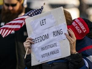 "A supporter of President Donald Trump holds a MAGA hat and sign reading ""Let freedom ring, investigate voter fraud"" as conservative demonstrators gather at the Washington State Capitol on January 10, 2021 in Olympia, Washington. David Ryder / GETTY IMAGES NORTH AMERICA / Getty Images via AFP"