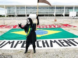 A demonstrator representing the grim reaper standing in front of an 'impeachment' banner takes part in a protest against Brazil's President Jair Bolsonaro measures to confront the COVID-19 coronavirus pandemic, January 17. (AFP)