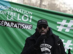 "A member of the anti-negrophobia brigade named Issa speaks as protesters demonstrate against a bill dubbed as ""anti-separatism"", in Paris on February 14, 2021. GEOFFROY VAN DER HASSELT / AFP"