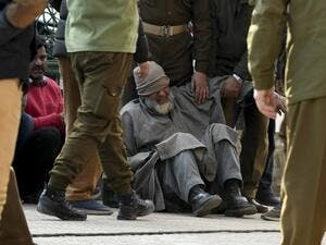 A relative (C) of a slain policeman griefs before a wreath laying ceremony at a police headquarter in Srinagar on February 19, 2021 after unidentified gunmen killed two police personnel in Srinagar. TAUSEEF MUSTAFA / AFP