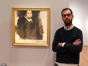 Pierre Fautrel, a member of the French art collective Obvious, poses in front of 'Portrait d'Edmond Belamy,' an image created using artificial intelligence that sold for a whopping £337,000 in 2018. (AFP)