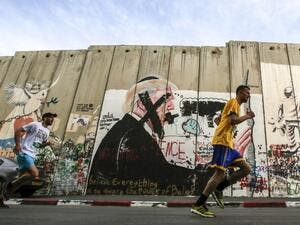 Participants run past a mural depicting U.S. President Donald Trump drawn along Israel's controversial separation barrier, which divides the West Bank from Jerusalem, in the biblical town of Bethlehem during the 6th International Palestine Marathon on Mar. 23, 2018. 