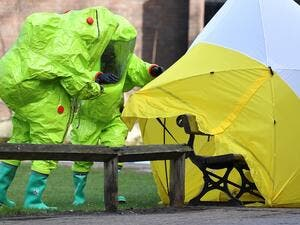 (FILES) In this file photo taken on Mar. 8, 2018 members of the emergency services in green biohazard encapsulated suits afix the tent over the bench where where former Russian spy Sergei Skripal and his daughter Yulia were found on Mar. 4 in critical condition at The Maltings shopping centre in Salisbury, southern England, after the tent became detached. (Ben STANSALL / AFP)