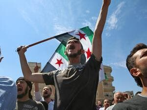 Syrian protesters wave the flag of the opposition as they demonstrate against the regime and its ally Russia, in the rebel-held city of Idlib on September 7, 2018 (ZEIN AL RIFAI/AFP)