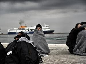 Children wrapped in covers stand in a harbour as migrants and refugees arrive on the Greek island of Lesbos while crossing the Aegean Sea from Turkey on March 2, 2016, in Mytilene. (AFP/Aris Messinis)