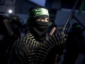 A member of the Ezzedine al-Qassam Brigades, the military wing of the Palestinian Islamist movement Hamas holds his weapon during a rally to mark the 12th anniversary of the death of assassinated Hamas spiritual leader Sheikh Ahmed Yassine on March 23, 2016 outside his home in Gaza city. (AFP/Mahmud Hams)