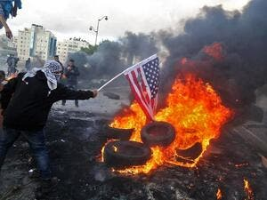 A Palestinian protester sets alight an America flag during clashes with Israeli troops at a protest against President Trump's decision to recognize Jerusalem as the capital of Israel. (ABBAS MOMANI / AFP)