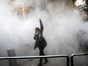 An Iranian woman raises her fist amid the smoke of tear gas at the University of Tehran during a protest driven by anger over economic problems in the capital Tehran on Dec. 30, 2017 (STR / AFP)