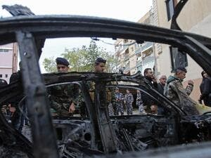 Lebanese security forces check a damaged vehicle following a car bomb blast in the southern Lebanese port city of Sidon on Jan. 14, 2018 (Mahmoud ZAYYAT / AFP)