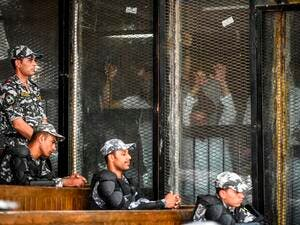Members of Egypt's banned Muslim Brotherhood are seen inside a glass dock during their trial in the capital Cairo on July 28, 2018. (AFP/Khaled Desouki)
