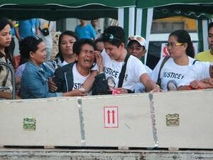 Eva (3rd L), the mother of Filipina worker Joanna Demafelis whose body was found inside a freezer in Kuwait, cries in front of the wooden casket containing her daughter's body shortly after its arrival from Manila at Iloilo International Airport in Iloilo province, central Philippines, on Feb. 17, 2018. (AFP)