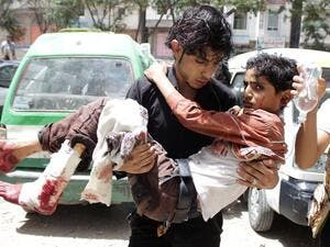 A man carries an injured child from fighting in Taiz (Source: AFP)