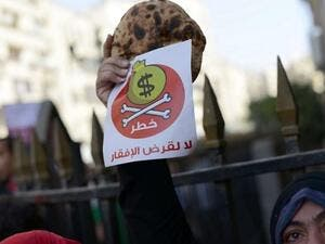 Egyptian protester holds bread along with a flyer in Arabic that reads 'Danger, no to loans that lead to poverty' during a rally in downtown Cairo on April 3, 2013. (AFP/Khaled Desouki)