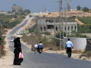 A Palestinian woman waits to be picked up on a road between the coast and the former Jewish settlement of Netzarim, south of Gaza City. (AFP/File)