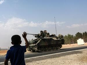 A Turkish boy waves to Turkish tank convoy driving into Syria from the border city of Karkamis in the southern region of Gaziantep, on August 26, 2016. (AFP/Bulent Kilic)