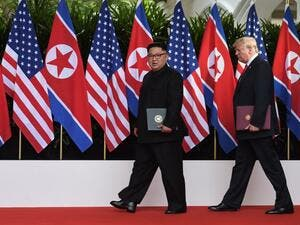 US President Donald Trump (R) walks out with North Korea's leader Kim Jong Un (L) after taking part in a signing ceremony at the end of their historic US-North Korea summit, at the Capella Hotel on Sentosa island in Singapore on June 12, 2018/AFP