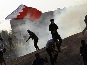 Bahraini protesters clash with police as they are sprayed with tear gas. [AFP]
