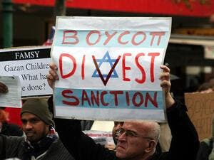Protesters hold placards in support of the Boycott, Divestment, and Sanctions (BDS) movement. (Wikimedia)