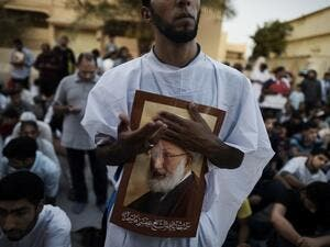 Bahraini protesters hold posters of Sheikh Qassim in June, after Bahraini authorities stripped him of his citizenship. (AFP/File)