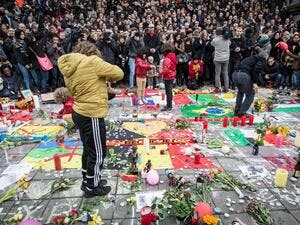 People gather to observe a minute of silence in memory of the victims of the Brussels airport and metro bombings, on the Place de la Bourse in central Brussels, on March 23, 2016, a day after the triple blasts killed some 30 people and left around 250 injured. (AFP/Aurore Belot)