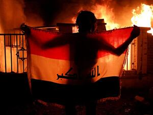 Man holding a national flag while demonstrators burn municipal complex (Twitter)