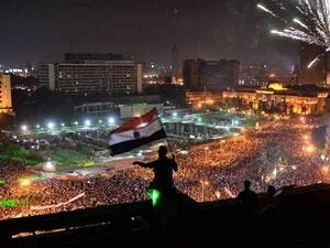 Egyptians wave the national flag on a building rooftop on July 7, 2013 as hundreds of thousands flood Egypt's landmark Tahrir square to demontrate against ousted President Mohammed Morsi and in support of the Egyptian Army in Cairo (Mohamed el-Shahed / AFP)