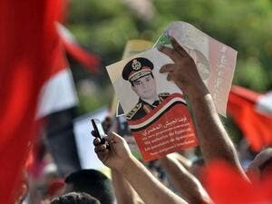 EGYPT, Cairo : Egyptian opponents of deposed president Mohamed Morsi hold up a poster of army chief General Abdel Fattah el-Sisi on July 26, 2013 during a protest in Cairo. AFP PHOTO/MOHAMED EL-SHAHED