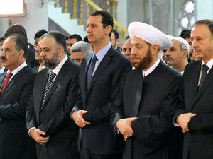 A handout picture released by the official Syrian Arab News Agency (SANA) on October 15, 2013 shows President Bashar al-Assad (C) and Syrian Grand Mufti Ahmed Hassun (C-R) praying at the Sayeda Hassiba mosque in the capital Damascus. (Image credit: AFP)
