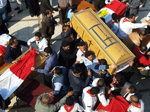 Egyptian clergymen and officials carry the coffins of the victims of a church bombing in Cairo, on December 12, 2016. (AFP/Khaled Desouki)