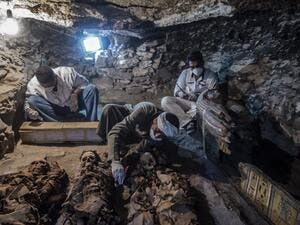 A picture taken on September 9, 2017 shows Egyptian labourers and archaeologists unearthing mummies at a newly-uncovered ancient tomb for a goldsmith. (Khaled Desouki/AFP)